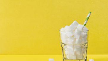 bicchiere riempito con zollette di zucchero